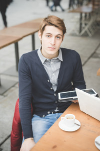 Young handsome caucasian contemporary businessman seated on a bar using a smartphone looking in camera - technology, network, business, finance concepts