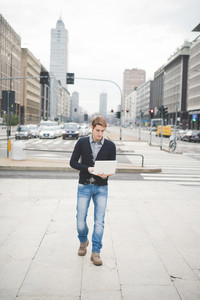 Young handsome caucasian contemporary businessman walking on the street using a notebook looking down the screen - technology, network, business, finance concepts