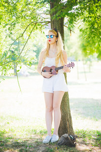 young handsome caucasian long blonde straight hair hippy woman posing leaning against a tree in a city park, playing a ukulele, overlooking, pensive - music, inspiration concept