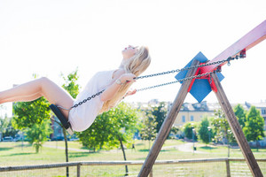 young handsome caucasian long blonde straight hair woman having fun on a seesaw in a playground eyes closed - childhood, freshness, carefree concept