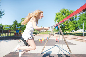 young handsome caucasian long blonde straight hair woman having fun on a seesaw in a playground eyes closed laughing - childhood, freshness, carefreeness concept