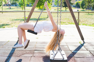 young handsome caucasian long blonde straight hair woman having fun on a seesaw in a playground eyes closed, serene - childhood, freshness, carefreeness concept