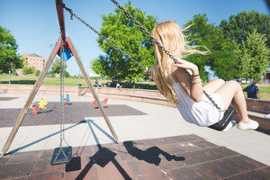 young handsome caucasian long blonde straight hair woman having fun on a seesaw in a playground having fun - childhood, freshness, carefreeness concept