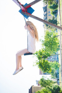 young handsome caucasian long blonde straight hair woman having fun on a seesaw in a playground looking in camera, eyes closed - childhood, freshness, carefreeness concept - picture rotate