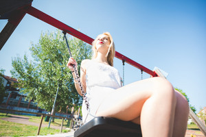 young handsome caucasian long blonde straight hair woman having fun on a seesaw in a playground looking in camera, smiling - childhood, freshness, carefree concept