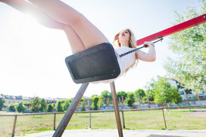 young handsome caucasian long blonde straight hair woman having fun on a seesaw in a playground looking upward - childhood, freshness, carefreeness concept
