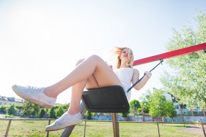 young handsome caucasian long blonde straight hair woman having fun on a seesaw in a playground looking upward, laughing - childhood, freshness, carefree concept