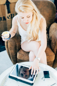 young handsome caucasian long blonde straight hair woman sitting on a bar, using a tablet, eating an ice cream, looking downward - technology, social network, relaxing concept