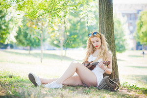 young handsome caucasian long blonde straight hair woman sitting on a city park playing with a ukulele pensive - music, artist, inspiration concept