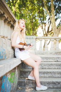 young handsome caucasian long blonde straight hair woman sitting on a small wall, playing with ukulele, overlooking right, eyes closed - music, inspiration concept