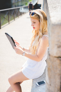 young handsome caucasian long blonde straight hair woman sitting on a small wall, using smartphone and tablet, looking downward the screen, tapping - technology, social network, communication concept