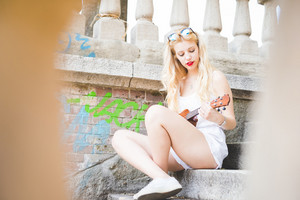 young handsome caucasian long blonde straight hair woman sitting on a staircase, playing with ukulele, looking downward the instrument - music, inspiration concept