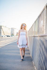 young handsome caucasian long blonde straight hair woman walking in the city, overlooking left - wearing white dress and sunglasses