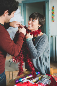 Young handsome caucasian man and woman couple playing with christmas decoration - happiness, christmas, couple concept