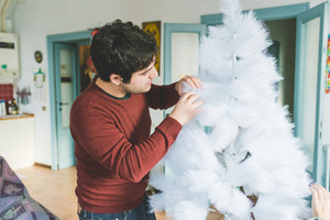 young handsome caucasian man assembling christmas tree, looking downward, concentrate - christmas, holiday, winter concept