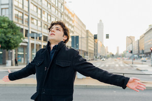 Young handsome caucasian man feeling free spreading arms outdoor in the city sunset - freedom, free, serene concept