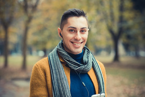 young handsome caucasian man in autumn park outdoor - using smartphone with earphones