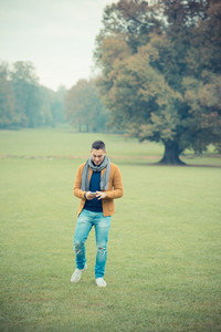 young handsome caucasian man in autumn park outdoor - using smartphone