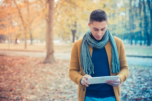 young handsome caucasian man in autumn park outdoor - using tablet device connected wireless