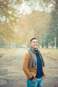 young handsome caucasian man in autumn park outdoor