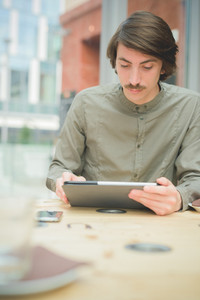 Young handsome caucasian man with moustache seated on a bar using technological devices like smartphone and tablet looking the screen - technology, communication, social network concept