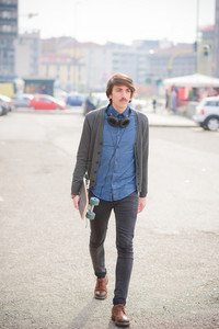 Young handsome caucasian man with moustache walking through the streets with a skate listening to music by headphones - sportive, music, relaxing concept