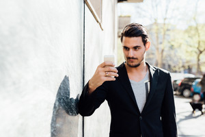 Young handsome caucasian millennial man outdoor in the city using smart phone hand hold taking selfie - vanity, social network, technology concept