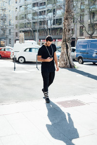 Young handsome caucasian millennial man walking outdoor in the city using smart phone hand hold looking the screen - technology, social network, communication concept