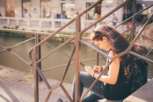 Young handsome caucasian reddish brown hair woman seated on a staircase using a smartphone - technology, social network, communication concept - dressed with black shirt and blue jeans