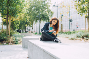 Young handsome caucasian reddish hair woman sitting on a small wall, listening music with headphones and smartphone handhold - music, relax, technology concept