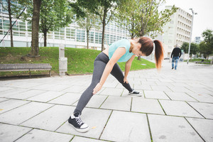 young handsome caucasian reddish straight hair woman doing stretching outdoor in the city, legs open, hands on her knee, looking downward - training, sportive, healthy concept