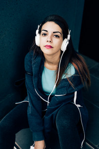 young handsome caucasian reddish straight hair woman sitting on a step listening music with headphones and smartphone handhold, looking in camera, thoughtless - music, technology, happiness concept