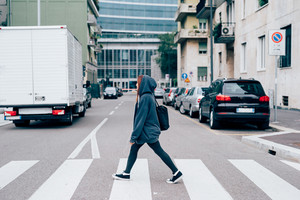 young handsome caucasian reddish straight hair woman walking through the street of the city on pedestrian crossing, looking straight, wearing sweatshirt with hood on her head