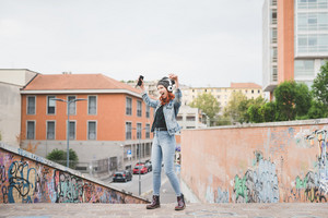 Young handsome caucasian redhead straight hair woman dancing outside in the city, listening music with headphones and smartphone handhold laughing and singing - music, relax, technology concept