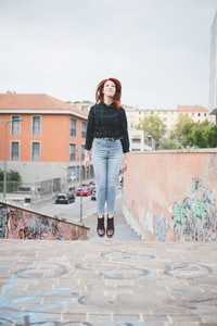 Young handsome caucasian redhead straight hair woman jumping on the spot, looking upward, smiling - athletic, carefree, youth concept