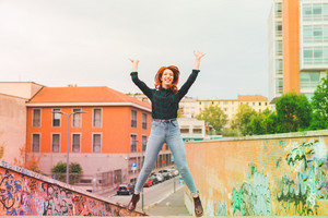 Young handsome caucasian redhead straight hair woman jumping outdoor in the city, hands up, laughing - girl power, goal, success concept - colorful filtered