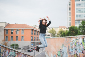 Young handsome caucasian redhead straight hair woman jumping outdoor in the city, hands up, laughing - girl power, goal, success concept
