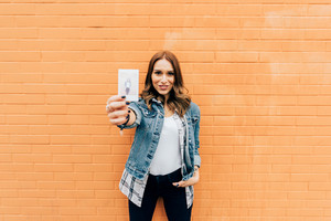 Young handsome caucasian redhead straight hair woman posing leaning against a brick wall, showing a polaroid of herself, taken with instant camera - photography concept