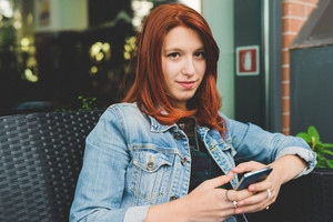 Young handsome caucasian redhead straight hair woman sitting on a chair in a bar, using a smartphone handheld, in camera smiling - technology, social network, communication concept