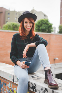 Young handsome caucasian redhead straight hair woman sitting on a small wall, holding a smartphone, looking in camera, laughing - technology, social network, communication concept