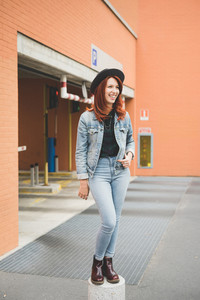 Young handsome caucasian redhead straight hair woman standing on a cement block, overlooking left, laughing, wearing pants and jeans jacket - youth, carefree, happiness concept