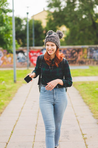 Young handsome caucasian redhead straight hair woman standing still, looking in camera, wearing jeans, blue and green shirt and hat, overlooking serene - youth, carefree concept