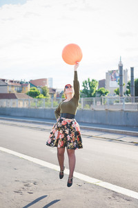 young handsome caucasian redhead woman jumping, playing with orange balloon, hand on her hips, looking up - youth, childhood concept - wearing floral skirt and green shirt