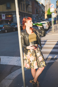 young handsome caucasian redhead woman leaning against a pole, drinking a beer, holding a smartphone - youth, technology, relaxing concept - wearing leather jacket, green shirt and floral skirt
