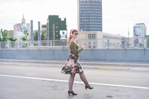 young handsome caucasian redhead woman listening music with headphones and smartphone, dancing in the city, smiling - relaxing, dancing, carefreeness concept - wearing green shirt, floral skirt