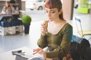 Young handsome caucasian redhead woman sitting in a bar using tablet while eating ice cream, looking downward - technology, social network, multitasking concept
