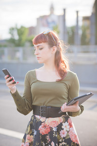 Young handsome caucasian redhead woman using a smartphone, looking downward and tapping the screen while holding a tablet on the other hand - multitasking, working, technology concept - backlight