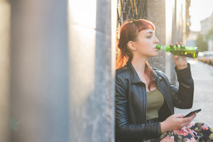 Young handsome caucasian redhead woman using smartphone drinking a beer and using a smartphone, overlooking left and tapping the screen - social network, technology, communication concept - backlight