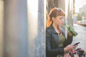 Young handsome caucasian redhead woman using smartphone holding a beer looking down and tapping the screen - social network, technology, communication concept - backlight
