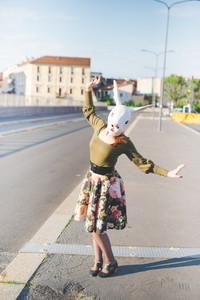 young handsome caucasian redhead woman with rabbit mask, dancing in the street of the city, holding a strip of her floral skirt - absurd, strange, dreamlike concept